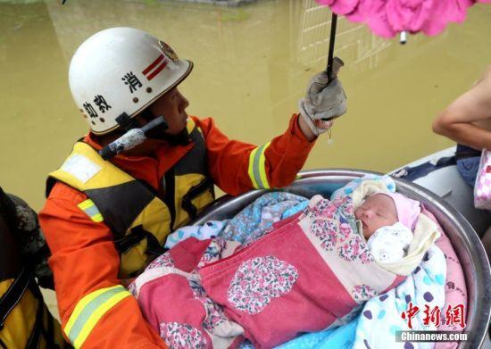 由于连日降雨,贵州沿河县甘溪镇唐边村下坝村民组整个村庄被水淹。6月21日,当地消防部门利用冲锋舟救援一家三口,消防员用一个大水盆装下刚出生10天的婴儿,做好双重保护,而正在坐月子的母亲不能沾水,消防员与其丈夫将其抬上冲锋舟。在冲锋舟上,遮阳伞下,婴儿安然入睡。图为消防将一家三口疏散到安全地带。中新社发 柯友川 摄
