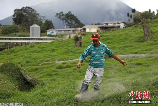 圣何塞的居民清理草地里的火山灰。