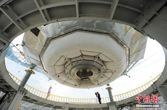 9月25日,世界最大单口径射电望远镜――500米口径球面射电望远镜(简称FAST)在贵州平塘县克度镇喀斯特洼坑中落成。图为9月24日,两名记者在FAST馈源舱底部进行现场报道。中新社记者 贺俊怡 摄