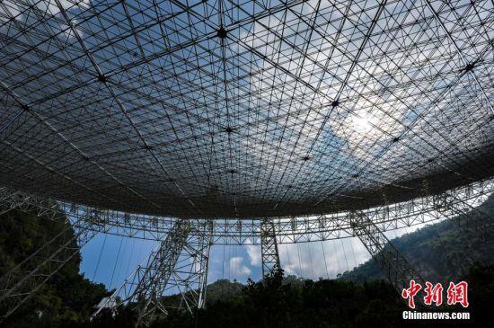 9月25日,世界最大单口径射电望远镜――500米口径球面射电望远镜(简称FAST)在贵州平塘县克度镇喀斯特洼坑中落成。图为9月24日,透过反射面板可见蓝天白云。中新社记者 贺俊怡 摄
