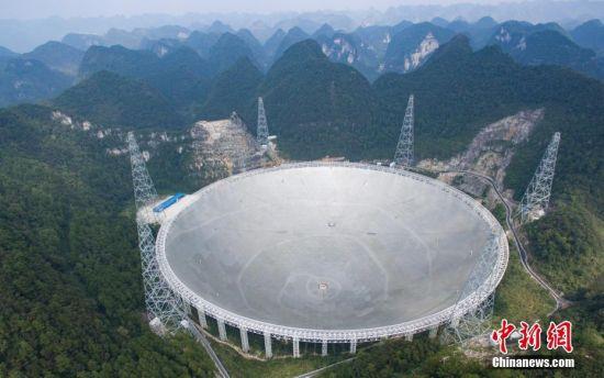 9月25日,世界最大单口径射电望远镜――500米口径球面射电望远镜(简称FAST)在贵州平塘县克度镇喀斯特洼坑中落成。图为9月24日航拍落成前夕的FAST。中新社记者 贺俊怡 摄