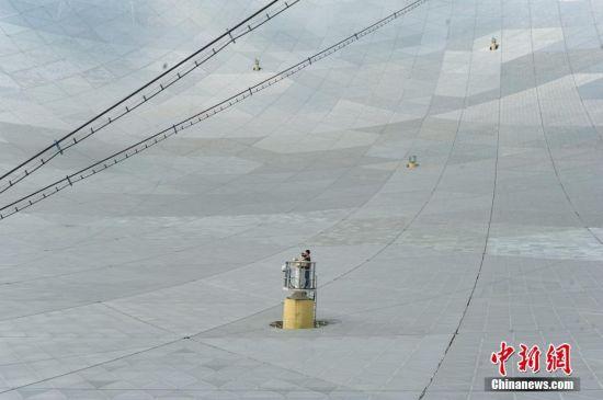 9月25日,世界最大单口径射电望远镜――500米口径球面射电望远镜(简称FAST)在贵州平塘县克度镇喀斯特洼坑中落成。图为9月24日,一名记者在测量基墩上工作。中新社记者 贺俊怡 摄
