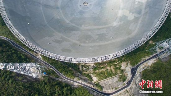 9月25日,世界最大单口径射电望远镜――500米口径球面射电望远镜(简称FAST)在贵州平塘县克度镇喀斯特洼坑中落成。图为9月24日航拍的FAST。中新社记者 贺俊怡 摄