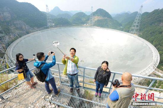 9月25日,世界最大单口径射电望远镜――500米口径球面射电望远镜(简称FAST)在贵州平塘县克度镇喀斯特洼坑中落成。图为9月24日,记者与FAST合影留念。中新社记者 贺俊怡 摄