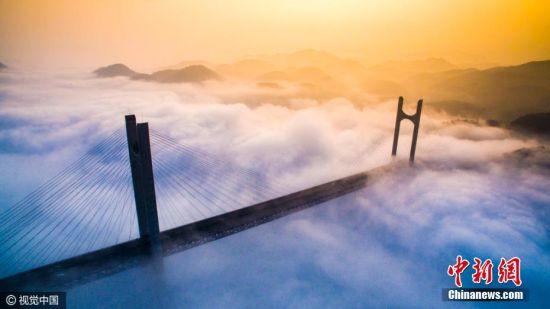 2016年10月7日,湖北恩来恩黔高速公贡水河大桥云雾缭绕。恩来恩黔高速公路贡水河大桥位于宣恩县晓关侗族乡倒洞塘村,是国内目前最大跨度的高速公路钢桁加劲梁斜拉桥,主跨400米,全桥长1063米。全桥由两座主塔、钢桁梁主桥、南北两岸引桥构成。主塔高达245米,由11240吨钢桁梁拼装组成。该桥已于2014年12月26日全线建成通车。图片来源:视觉中国