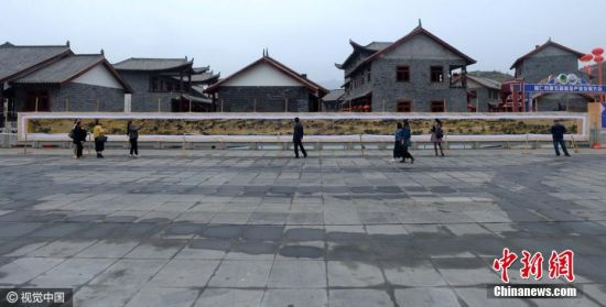 2016年10月17日,贵州省铜仁地区,在贵州省松桃苗族自治县九龙湖广场上,来自铜仁市江口县的妇女邓均芬展出自已从2011年正月起至2016年5月24日,耗时5年时间,一针一线地绣出的一幅长33米,宽1.5米的《清明上河图》,令不少参观者惊叹不已。图片来源:视觉中国