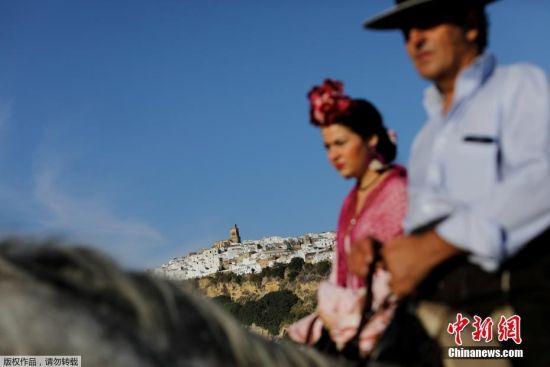 朝圣者骑行穿过白色村庄,前往罗梅拉尔山天主教圣殿。