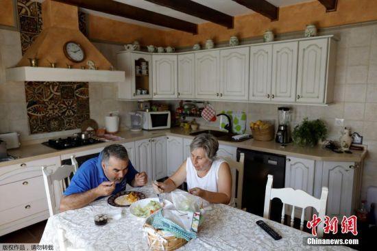 50岁的Maria Jose Manzano和其57岁的丈夫Joaquin Cortijo在房间内享用早餐。
