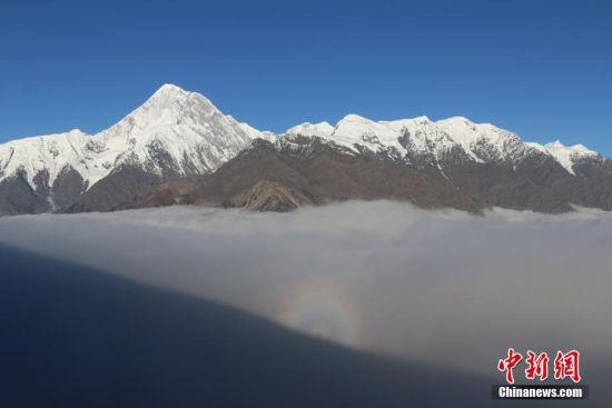 """10月22日下午,在四川贡嘎山主峰西坡下的云海中出现罕见""""佛光"""",时间长达约30分钟。佛光出现过程中,云海快速升腾,瞬间隐没贡嘎山主峰和周围群山,几分钟后,覆盖主峰的云雾散去,云海中的""""佛光""""依然可以看见,蔚为壮观。""""佛光""""是一种光的折射现象。中新社发 羊慧明 摄"""