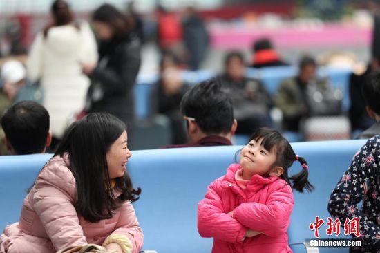 """1月13日,2017年春运大幕开启,""""小候鸟""""们也踏上了返程之旅。图为贵阳北站,小女孩与家人游戏。 中新社记者 贺俊怡 摄"""