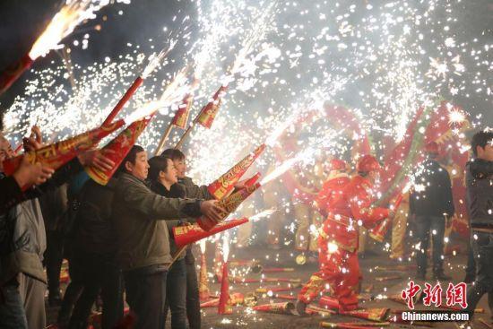 民众对着舞动的龙喷射烟花,喜迎元宵佳节。 中新社记者 贺俊怡 摄