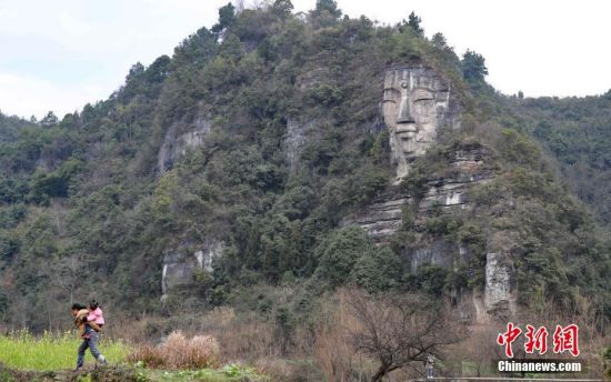 2月13日,下水村村民从佛像对面的田埂上走过。这座由天然巨石雕凿形成的佛像坐落在贵阳市白云区下水村,佛像身高约50米,头高16米,坐东向西,佛身则是依山就势的一块块石岩石板叠成。中新社记者 贺俊怡 摄