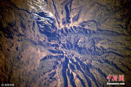 """2017年3月20日消息,法国宇航员Thomas Pesquet在太空执行任务期间用相机记录了从太空俯瞰到的地球景观,在他的镜头下,俄罗斯雪地好似极简主义画家笔下的抽象画;沙特阿拉伯沙漠上的灌溉盛况如绿色豌豆铺洒又似一盘盘光碟;闻名世界的美国大峡谷不再""""大得难以想象"""";阿尔卑斯山上的积雪犹如凸起的鸡蛋白。Thomas从独特视角向人们展示了地球母亲的震撼美景。图片来源:视觉中国"""
