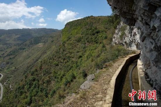 """""""大发渠""""经过3个村庄、十余个村民组,横跨三座大山,三道绝壁,主渠长7200米,支渠长2200米,其中有170多米悬挂在寸草不生的绝壁上。"""