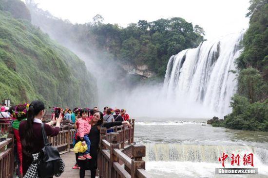 壮观瀑布吸引游客前来观赏。 中新社记者 贺俊怡 摄