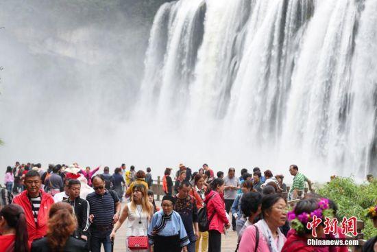 大批游客前来观赏丰水期的黄果树大瀑布。 中新社记者 贺俊怡 摄