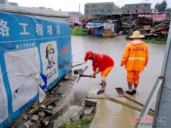 图为二甫养护站职工雨中疏通边沟。