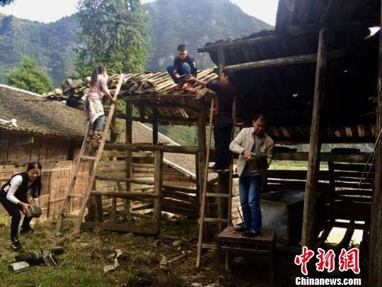 """江口驻村""""第一书记""""向丽与同事帮助贫困户修缮房屋。 江轩 摄"""