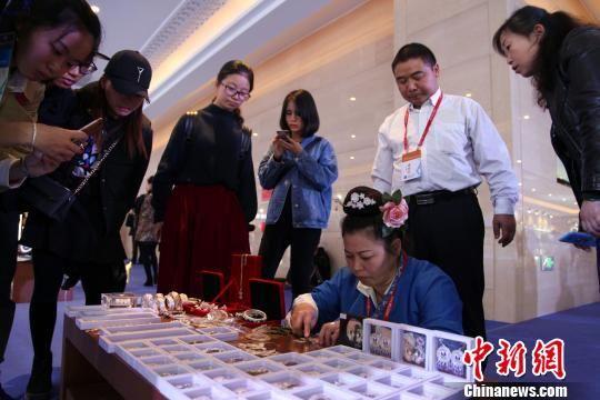 图为贵州苗族传统手工艺人正在现场制作苗族银饰,吸引民众围观。 瞿宏伦 摄
