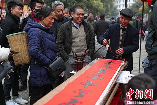 2月12日,乡场上,民众围在写对联的小摊旁,有说有笑。 中新社记者 贺俊怡 摄
