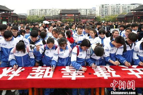 学生在活动标语上签名。中新社记者 贺俊怡 摄