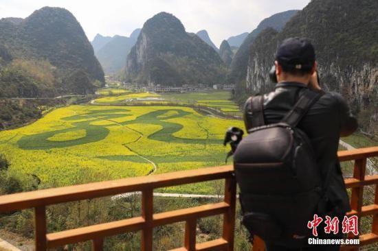 """资料图:摄影爱好者正在拍摄""""龙字田""""。当日,贵州省安顺市龙宫漩塘景区田野间巨大的繁体""""龙""""字清晰可见,吸引民众和游客踏青游玩。中新社记者 瞿宏伦 摄"""