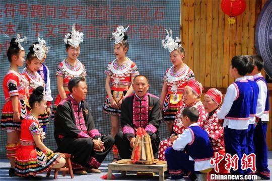 国家级非物质文化遗产项目刻道传承人吴通贤与民众表演苗族古歌。 李忠果 摄