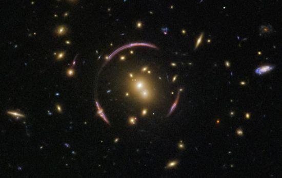 """爱因斯坦在20世纪初提出了广义相对论,在此基础上,爱因斯坦和其他几位科学家预言了""""引力透镜""""现象,即大质量天体(如星系团)会较大程度地扭曲周围时空,当背景光源(如星系)发出的光线从附近经过时,就会像通过透镜一样发生弯曲。 图片来源:NASA官网"""
