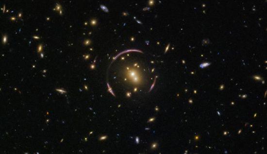 照片中可以看到,星系团SDSS J0146-0929严重扭曲了周围的时空,一个遥远星系的星光恰好从附近穿过,发生弯曲后传到地球,使得星系看上去呈环状。除了产生了古怪的形状之外,引力透镜还为天文学家们提供了最直接的探测椭圆星系中暗物质分布的方式。 图片来源:NASA官网