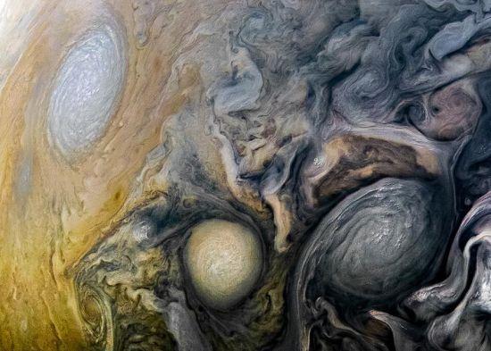 """近日,NASA在官网公布了由""""朱诺""""号木星探测器在4月1日拍摄的最新木星表面图像,这是""""朱诺""""号第12次飞越木星。图片显示了木星北半球独特的大气层漩涡,大小不一的涡旋如同一个个神秘的洞口,通往木星内部。 图片来源:NASA官网"""
