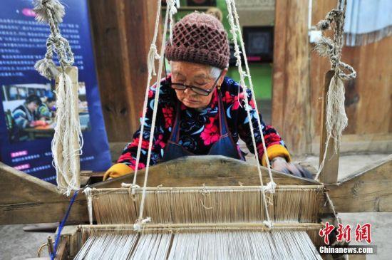 4月11日,一名年近九旬的老人在织布。当日,在贵州省织金县官寨苗族乡小妥倮村一家蜡染合作社内,蜡染手工艺人正在绘制蜡画。蜡染是织金苗族最普遍、最有名的工艺美术,当地居民通过老传少、母传女、或相互学习将蜡染技艺一代一代地传承下去。苗族蜡染于2015年1月入选贵州省人民政府非物质文化遗产传统技艺类名录。 中新社记者 陈威 摄