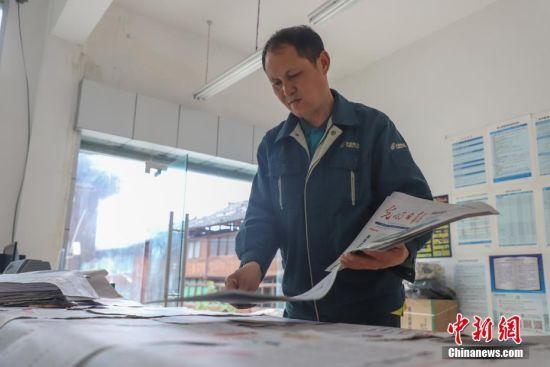 """4月12日,张林昌在代办点整理报刊,这是他每天的常规工作。张林昌是贵州省锦屏县邮政局启蒙支局乡村邮递员,他一人在莽莽群山之间送信已坚持了31年。31年里,靠着肩挑背扛,他累计将140多万件报刊信件送达深山的村民家中,步行里程已超过24万多公里。1987年,23岁的张林昌刚从部队退伍返乡就接过老邮员肩上的邮包干上了乡村邮递员工作,负责锦屏县河口乡片区的邮路。位于大山深处的邮路全长90余公里,串联着启蒙镇到河口乡一带2.5万余民众。这期间,他每年365天除了春节和偶尔有事请假,几乎从不缺席。按照规定,年近55岁的他可申请退休,但他却坚定地说""""只要我还能走,就会坚持给乡亲们送邮件!"""" 中新社发 瞿宏伦 摄"""