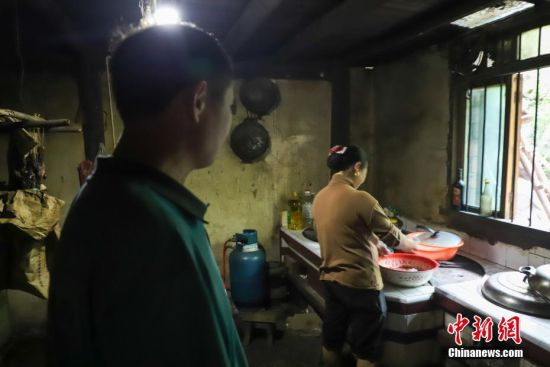 4月12日,张林昌与妻子在家中。因工作原因张林昌平时早出晚归,很少分担家务,他对妻子非常愧疚。 中新社发 瞿宏伦 摄