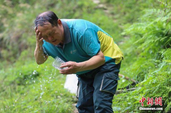 4月12日,行走在山林间,张林昌用山泉洗脸。 中新社发 瞿宏伦 摄