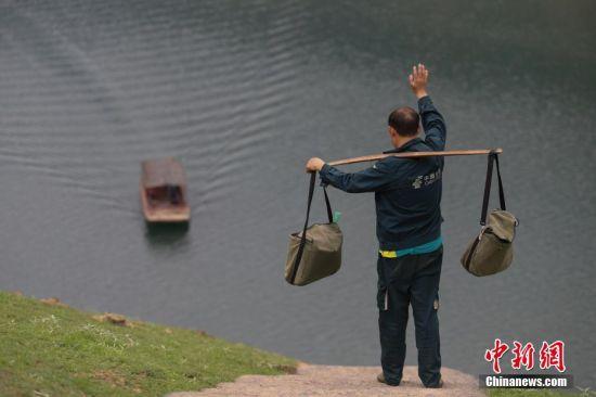 4月12日,张林昌向船家招手示意乘船。 中新社发 瞿宏伦 摄