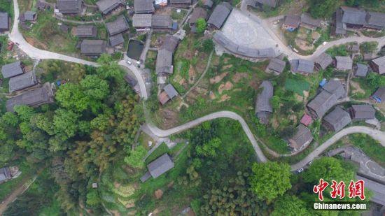 """4月13日,航拍苗寨内的乡间小道。文斗苗寨位于贵州省锦屏县西北部清水江河畔,坐落于大山梁上。苗寨民居顺依其势,星罗棋布于崇岭之间。它既是一颗镶嵌在清水江河畔的生态明珠,也是一部卷页厚重的生态历史,被学界誉为""""百年环保第一村""""和""""看得见历史的村寨""""。2012年该苗寨入选""""中国世界文化遗产预备名单"""",2014年入选""""中国传统村落""""。中新社记者 瞿宏伦 摄"""