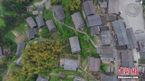 """4月13日,航拍苗寨错落有致的民居。文斗苗寨位于贵州省锦屏县西北部清水江河畔,坐落于大山梁上。苗寨民居顺依其势,星罗棋布于崇岭之间。它既是一颗镶嵌在清水江河畔的生态明珠,也是一部卷页厚重的生态历史,被学界誉为""""百年环保第一村""""和""""看得见历史的村寨""""。2012年该苗寨入选""""中国世界文化遗产预备名单"""",2014年入选""""中国传统村落""""。中新社记者 瞿宏伦 摄"""