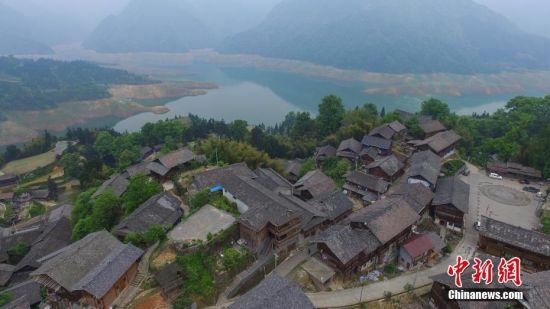 """4月13日,航拍依江而建的苗寨。文斗苗寨位于贵州省锦屏县西北部清水江河畔,坐落于大山梁上。苗寨民居顺依其势,星罗棋布于崇岭之间。它既是一颗镶嵌在清水江河畔的生态明珠,也是一部卷页厚重的生态历史,被学界誉为""""百年环保第一村""""和""""看得见历史的村寨""""。2012年该苗寨入选""""中国世界文化遗产预备名单"""",2014年入选""""中国传统村落""""。中新社记者 瞿宏伦 摄"""