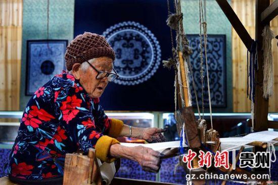 一名年近九旬的蜡染手工艺人在织布 龚小勇摄