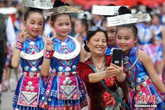 """4月28日,民众和巡游队伍中的小孩合影。当日,中国苗族姊妹节盛装巡游活动在贵州省黔东南州台江县举行。苗族姊妹节以苗族青年女子为中心,以邀约情人游方对歌、吃姊妹饭、跳芦笙木鼓舞、订立婚约等活动内容为主,被誉为""""最古老的东方情人节""""、""""藏在花蕊里的节日""""。中新社记者 瞿宏伦 摄"""