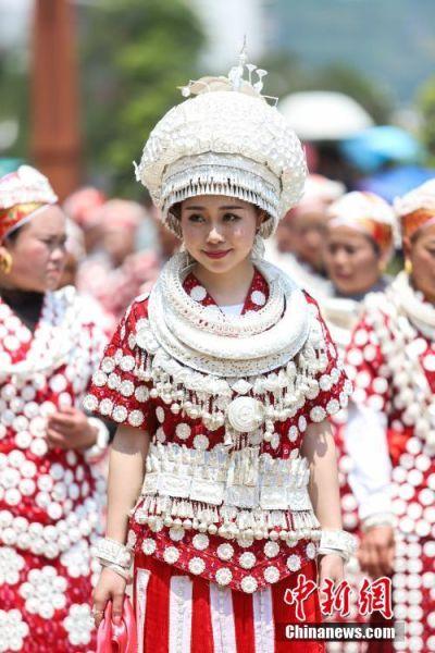 """4月28日,穿着白央支系苗族盛装的女孩。当日,中国苗族姊妹节盛装巡游活动在贵州省黔东南州台江县举行。苗族姊妹节以苗族青年女子为中心,以邀约情人游方对歌、吃姊妹饭、跳芦笙木鼓舞、订立婚约等活动内容为主,被誉为""""最古老的东方情人节""""、""""藏在花蕊里的节日""""。中新社记者 瞿宏伦 摄"""