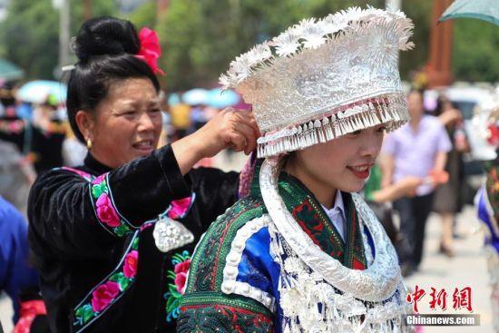 """4月28日,家人正在为苗族女孩整理头饰。当日,中国苗族姊妹节盛装巡游活动在贵州省黔东南州台江县举行。苗族姊妹节以苗族青年女子为中心,以邀约情人游方对歌、吃姊妹饭、跳芦笙木鼓舞、订立婚约等活动内容为主,被誉为""""最古老的东方情人节""""、""""藏在花蕊里的节日""""。中新社记者 瞿宏伦 摄"""
