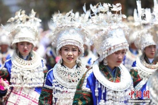 """4月28日,穿着华丽苗族服饰的巡游队伍。当日,中国苗族姊妹节盛装巡游活动在贵州省黔东南州台江县举行。苗族姊妹节以苗族青年女子为中心,以邀约情人游方对歌、吃姊妹饭、跳芦笙木鼓舞、订立婚约等活动内容为主,被誉为""""最古老的东方情人节""""、""""藏在花蕊里的节日""""。中新社记者 瞿宏伦 摄"""