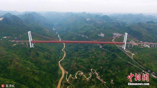 """6月5日,无人机高空拍摄的贵州关岭坝陵河大桥,该桥宛若钢铁巨龙,横跨峡谷天堑,雄伟壮观。 坝陵河大桥位于贵州省安顺市高原重丘区关岭县关索镇,是沪瑞国道主干线上跨越坝陵河大峡谷的第一座特大型桥梁。该桥为主跨1088米的单跨钢桁加劲梁悬索桥,桥梁全长1564米,桥面至坝陵河水面370米,建成时是居""""国内第一,世界第六""""的大跨径钢桁梁悬索桥,是贵州有史以来修建的技术含量最高的桥梁。2017年11月,坝陵河大桥获得中国建设工程鲁班奖。秦刚 摄 图片来源:东方IC 版权作品 请勿转载"""