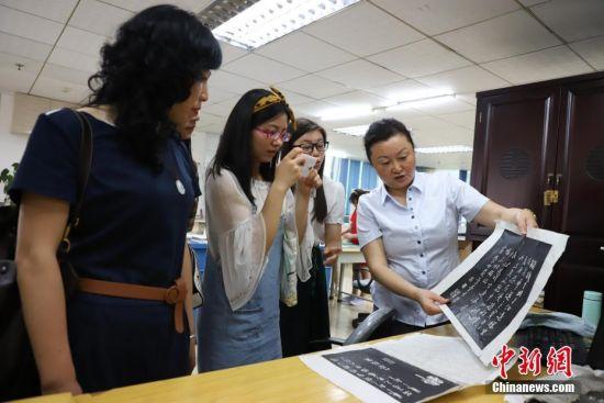 6月9日,古籍修复师王晓红在给民众展示拓片。 中新社发 瞿宏伦 摄