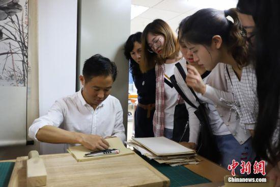 古籍修复师在给民众展示古籍装帧技艺。 中新社发 瞿宏伦 摄
