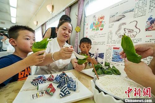 一名乘务员教小朋友包粽子。 中新社记者 贺俊怡 摄