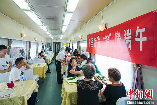 旅客在车厢内包粽子。 中新社记者 贺俊怡 摄