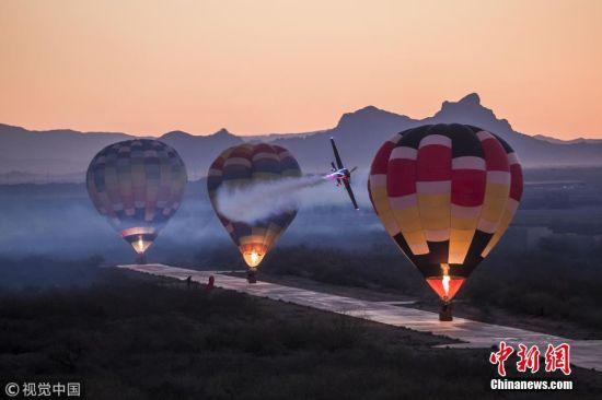 当地时间6月5日,在美国亚利桑那凤凰城,特技飞行员Kirby Chambliss驾驶飞机用急转弯的方式连续绕过数个热气球。自印第安纳波利斯赛道举办第一次热气球比赛后99年,这位红牛特技飞行大赛的飞行员以这种新颖而又引人注目的方式来庆祝美国热气球日(6月5日)。58岁的Kirby Chambliss曾荣获两次特技飞行大赛世界冠军。 图片来源:视觉中国