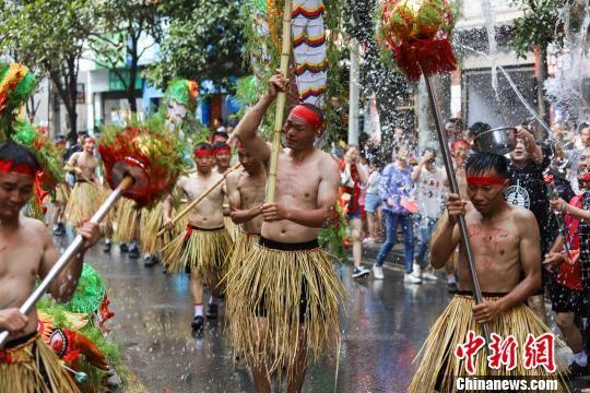 图为舞龙者在街道上舞水龙。 瞿宏伦 摄
